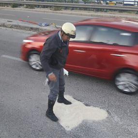 بالصور: عناصر قوى الأمن يردمون حفرة على الأوتوستراد